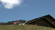 Stock Video Footage of Red tractor in the moutain, blue sky, one cloud and a chalet with zoom