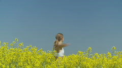 Young woman in rape field full of joy close Stock Footage
