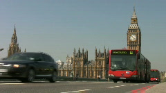 Big Ben clock tower and red bendy buses with black taxi cabs London Stock Footage