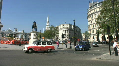 Black taxi cabs driving round Trafalgar Square in London England - stock footage