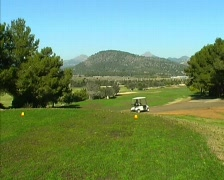 Golf fairway and caddy in the distance - stock footage
