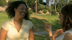 Two girl friends laughing and talking in the park. Version 2. - stock footage