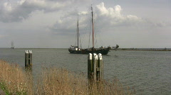 Sailing barge moves through a waterway - stock footage