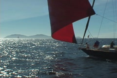 Sailing past a Pacific island with spinnaker - stock footage