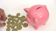 Stock Video Footage of Saving money in a piggy bank. Time lapse.