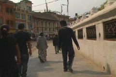 Bodanath people walking by prayer wheels Stock Footage