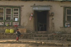 Sherpa toddler infront of house - stock footage