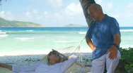 Senior couple relaxing under palmtrees Stock Footage