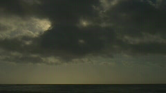 Sun rays briefly emerge from dark clouds in ocean timelapse Stock Footage