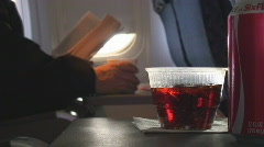 Soda fizzes in cup aboard airplane Stock Footage
