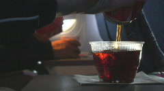Female hand pours fizzing soft drink aboard flight Stock Footage