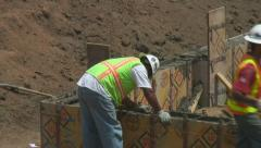 Concrete workers carefully smooth wet mix at top of wall forms. Stock Footage