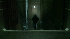 Hooded man walking up stairs - stock footage
