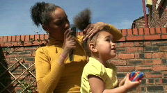 Mother brushing daughters hair Stock Footage