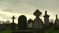 Hooded man walking past gravestones - stock footage