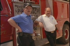 Firemen around firetruck Stock Footage
