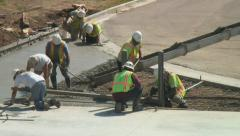 Concrete workers spread and flatten newly poured cement mix. - stock footage