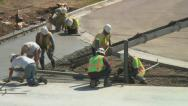 Concrete workers spread and flatten newly poured cement mix. Stock Footage