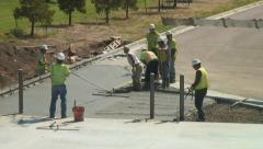 Concrete workers hustle to level and smooth newly poured cement mix. Stock Footage