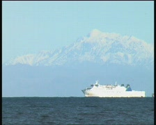 Ship passes in front of distant mountains Stock Footage