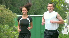Attractive young couple jogs in a park. Version 3. - stock footage