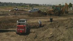 Backhoe frontloader and skid loader work to backfill new foundations with dirt. Stock Footage
