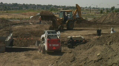 Tractors backfill foundation on new construction site. Stock Footage