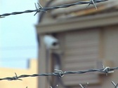 Rack Focus From A Barbed Wire Fence To Security Camera Stock Footage