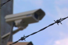 Rack Focus From A Barbed Wire Fence To Security Camera CU Stock Footage