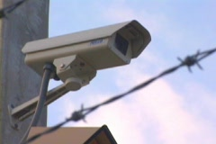 Tilt Upward of Security Camera Through Barbed Wire Stock Footage