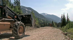 Backhoe on mountain road construction M HD Stock Footage
