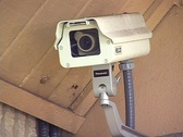Stock Video Footage of Security Camera Mounted on the Side of a Building