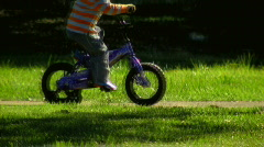 Young Child Riding Bike Through Suburban Park Stock Footage