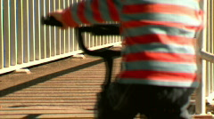 Young Child Riding Bike Across Narrow Bridge with Steel Railings - stock footage