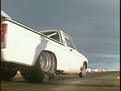 Motorsports, drag race white pickup launch low angle Stock Footage