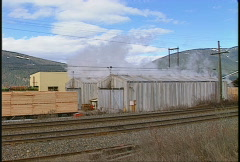 Lumber mill steam above kiln Stock Footage
