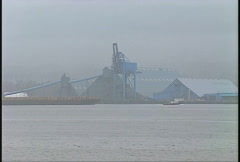Maritime transportation, tug and barge passing in front of industrial buildings Stock Footage
