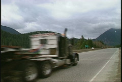 trucking, truck pulling road grader up hill - stock footage