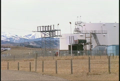 Oil & gas, fuel tanks on the prairie, mountains in background Stock Footage