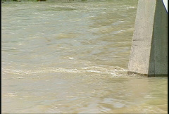 Muddy river and bridge abutment Stock Footage