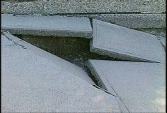 Flood damaged buckled sidewalk Stock Footage