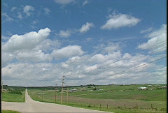 Country one-lane blacktop with clouds Stock Footage