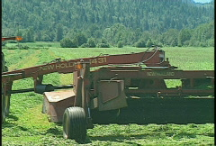 Agriculture, tractor harvesting green hay, #6 med, going away, mid summer Stock Footage