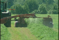 Agriculture, tractor harvesting green hay, #5 long shot, going away, mid summer Stock Footage