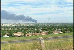 Fire, hub oil fire, huge plumes of black smoke, #16 from across city,  zoom in Stock Footage