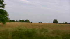 Wheat field with farmhouse in the background Stock Footage