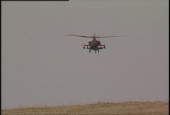 Military helicopter, AH64 Apache disappears behind hill Stock Footage