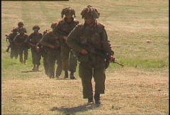 Military, armed soldiers walking through field Stock Footage