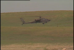 Military, hovering AH64 Apache helicopter, zoom back to soldiers Stock Footage