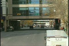 Downtown traffic under skywalk Stock Footage